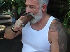 Viejo barbudo fumando puro