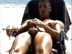 Wanking his huge cock on the beach