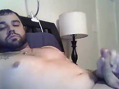 Sexy tattooed guy shooting on bed