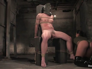 Mistress Sandra Romain's command of the male anatomy is made painfully clear as she casually hangs weights from her prisoner's stretched cock and balls during her interrogation. She is mercilessly taunting and sexy, and leaves the poor boy straining to find the words to please the demanding Mistress. Of course, no words suffice. She moves him into a position to receive her cock in his ass, but not before beating him to a ripe cherry color. His moans and pleading are met with a brutal ass fucking, and when she tires of this, she uses his face and cock for her pleasure. After the prisoner helplessly spills his load all over her beautiful tits, she makes him lick her clean and leaves him lapping up the last drops of semen from the spanking bench.