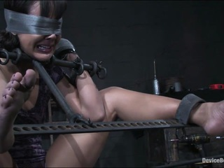 The clear plastic head harness is buckled on brutally tight, ensuring Jandi's screams won't get loud enough to irritate me. She tries to brace herself for the hard spanking and whipping she knows is coming her way in just a few seconds, but she can't find a position that offers any comfort. The steel bar she has been standing on is digging into the arch of her foot and the gag feels like it's cutting into her face. She starts to sweat, wondering how long she will be made to endure it. 5 minutes? 10? 30? 50? The situation is already unbearable as it is and I haven't even started to hurt her for real.