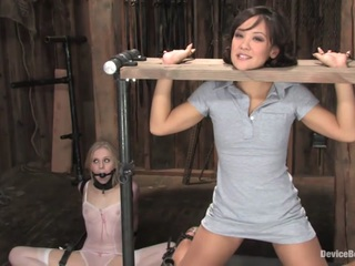 This is part one of Jandi Lin's live show. It's raw and brutal and everything a BDSM aficionado wants to see. Cyd Black and Claire Adams are relentless in their punishment of Jandi and Sarah Jane Ceylon. The show has barely started and Jandi's neck and hands are clamped in an upright wooden stock, getting her to kneel as far up as she can or else choke off her air. Each finger of either hand is bent back and tied off as hot wax is poured onto her tender palms, splashed on her breasts and elsewhere. Sarah watches from the floor where she is bound ankle to neck awaiting her turn to be punished.