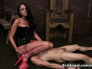 Raven Bay, a sexy brunette dungeon dominatrix in corset, fishnets and sky-high heels, restrains slave Eric Jover naked in stocks and makes him admit he's a piece of shit. She spews a scene-long streak of verbal filth. Raven slaps Eric's face hard and thrashes him with a riding crop; multiple serious, brutal kicks to his nut sac double him over in torment. She stands on him; sits on and spits in his face; and compares his pathetic pecker to Dirk Huge's humongous, black dick. Raven has Dirk join in degrading Eric's penis. She makes bitch-boy suck her feet and worship her ass while she's sucking a real man's cock. As Dirk plows her cunt, Raven chokes Eric and makes him thank Dirk. After her lover creams her face, Raven drools semen into Eric's mouth; he gargles and swallows!