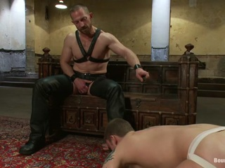 Adam Herst is new to the house and sub #316, Sebastian Keys is there to greet him . Adam is not impressed with the offering but decides to see what the boy is made of. After all, there must be some reason why he was given this slave. He has the boy work his leather. He inspects his ass and whacks it with his crop until it turns completely red. He's worth more testing so Adam covers him with brutal butterfly clamps, gets his cock hard, and flogs him. He rips the clips off, suspends him and flogs him until he screams for mercy. Suspended once again, #316 gets a massive cock ramed into his ass in mid air. He earns the new master's compliment by being able to lick his own load off of Adam's boot.